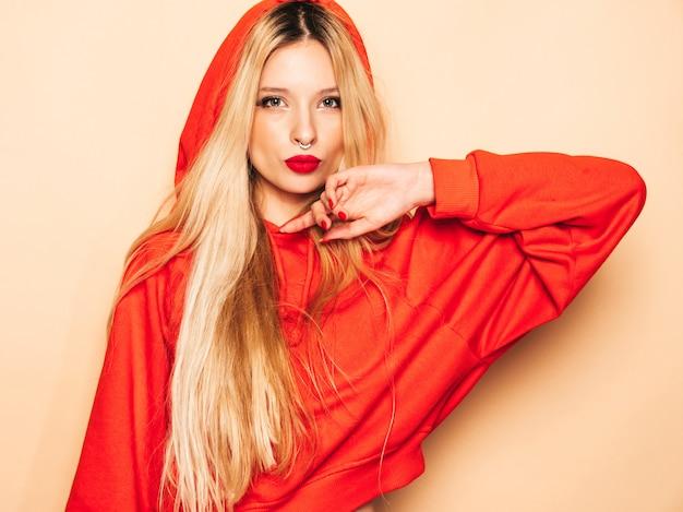 Porträt des jungen schönen bösen hipster-mädchens im trendigen roten kapuzenpulli und im ohrring in der nase. positives model, das spaß hat Kostenlose Fotos