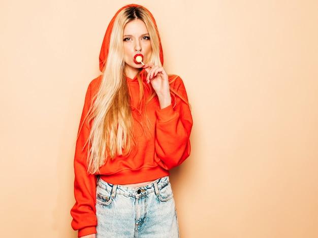 Porträt des jungen schönen bösen hipster-mädchens im trendigen roten kapuzenpulli und im ohrring in der nase. positives modell leckt runde kandiszucker Kostenlose Fotos