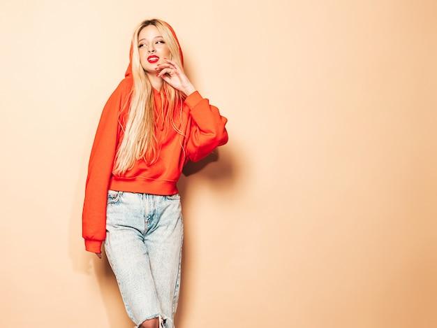Porträt des jungen schönen bösen hipster-mädchens im trendigen roten kapuzenpulli und im ohrring in der nase. positives modell Kostenlose Fotos