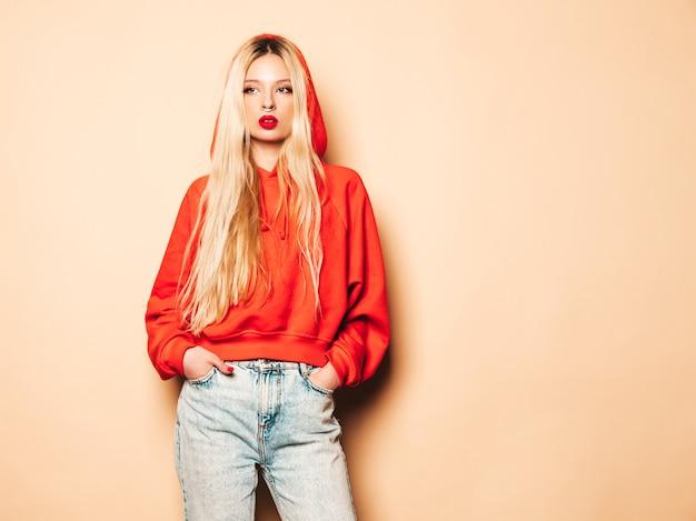 Porträt des jungen schönen hipster bösen mädchens im trendigen roten kapuzenpulli und im ohrring in der nase. sexy sorglose blonde frau, die im studio aufwirft. positives modell, das spaß hat Kostenlose Fotos
