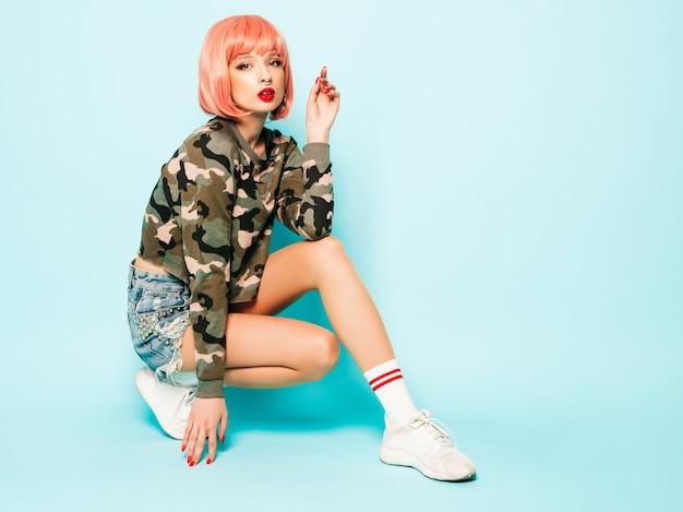 Porträt des jungen schönen hipster bösen mädchens in der trendigen roten sommerkleidung und im ohrring in der nase. sexy sorglose lächelnde frau, die im studio in der rosa perücke nahe der blauen wand sitzt. positives modell, das spaß hat Kostenlose Fotos