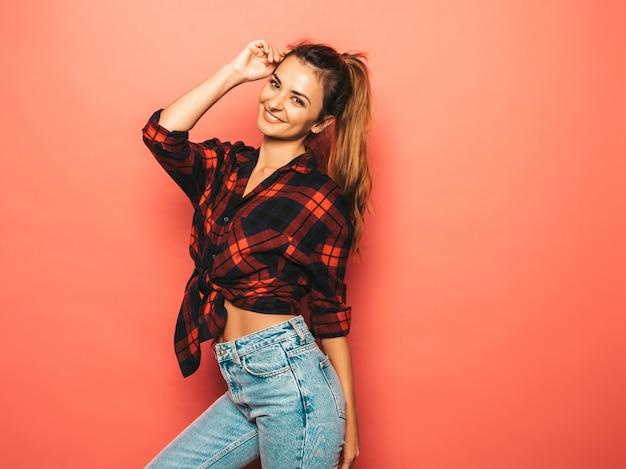Porträt des jungen schönen lächelnden hippie-mädchens im karierten hemd des modischen sommers und in den jeans kleidet. sexy sorglose frau, die nahe rosa wand im studio aufwirft. positives modell ohne make-up Kostenlose Fotos