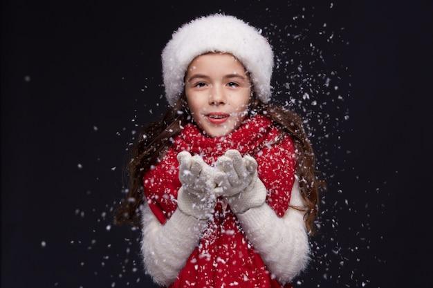 Porträt des jungen schönen lächelnden mädchens in rotem sankt-hut auf einem dunklen hintergrund Premium Fotos