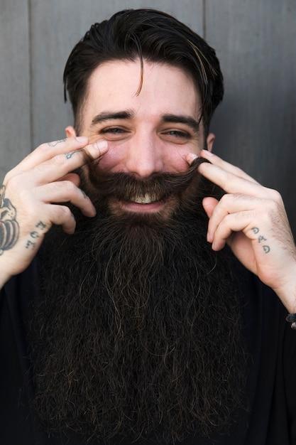 Porträt des jungen stilvollen bärtigen mannes, der schnurrbart wirbelt und kamera betrachtet Kostenlose Fotos