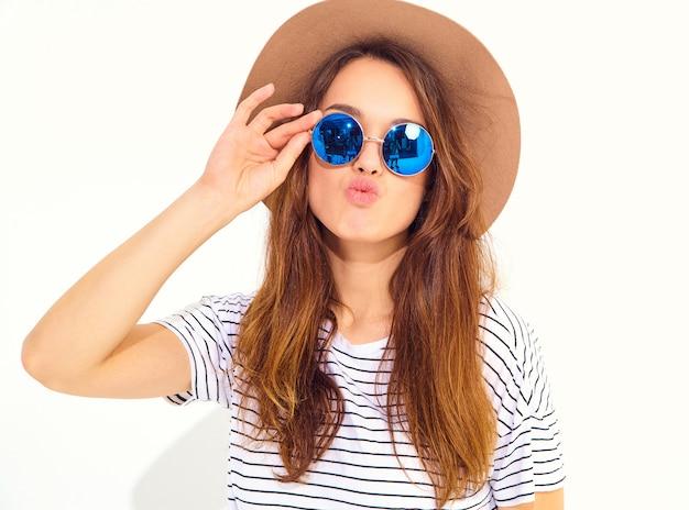 Porträt des jungen stilvollen lachenden frauenmodells im zufälligen sommer kleidet im braunen hut, der auf weißer wand lokalisiert wird Kostenlose Fotos