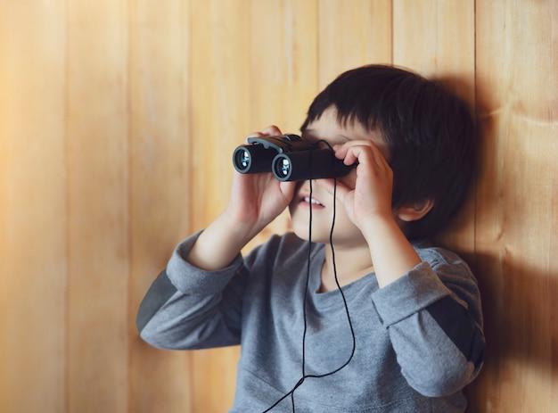 Porträt des jungenkindes, das durch ferngläser im ansichtspunkt der tierstation schaut, ein junger entdecker mit naturnatur im sommerlager Premium Fotos