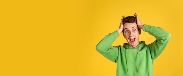 Porträt des kaukasischen jungen mannes auf gelber wand. schönes männliches modell im grünen outfit gestikulierend. konzept der menschlichen emotionen, gesichtsausdruck, verkauf, anzeige, jugend. copyspace. Kostenlose Fotos