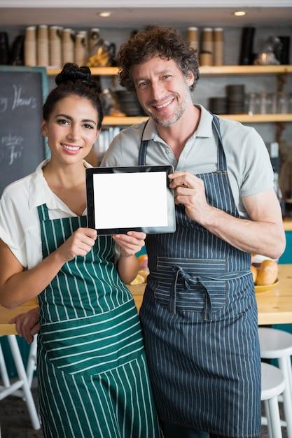 Porträt des kellners und der kellnerin, die digitales tablett halten Premium Fotos