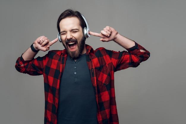 Porträt des kerls hörend musik mit kopfhörern Premium Fotos