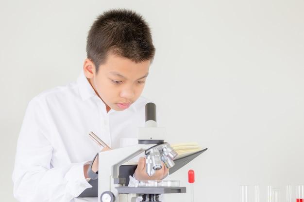 Porträt des kinderjungen, der mikroskop in der wissenschaftsstunde am labor verwendet und die ergebnisse notiert Premium Fotos