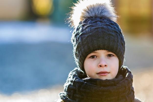 Porträt des kinderjungen in der mütze und im schal draußen im sonnigen wintertag Premium Fotos