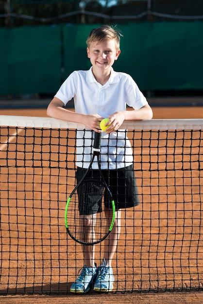 Porträt des kindes auf dem tennisfeld Kostenlose Fotos