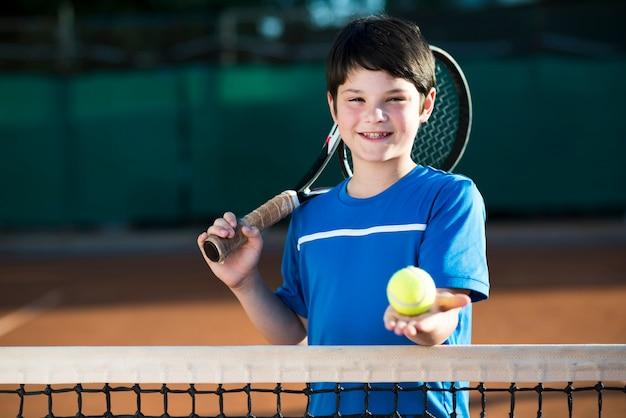 Porträt des kindes einen tennisball in der hand halten Kostenlose Fotos