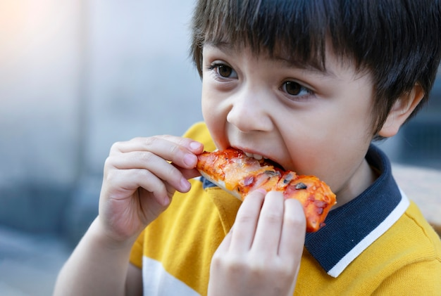 Porträt des kindes nach hause gemachtes café der pizza draußen essend Premium Fotos