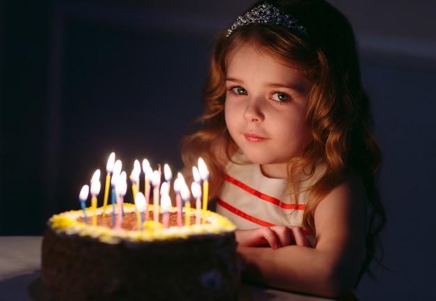 Porträt des kleinen hübschen mädchens mit geburtstagskuchen Premium Fotos