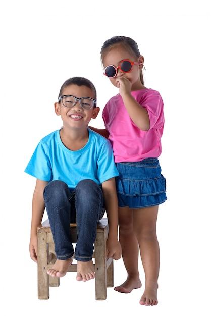 Porträt des kleinen jungen und des mädchens ist buntes t-shirt mit den gläsern, die auf weiß lokalisiert werden Premium Fotos