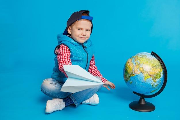 Porträt des kleinen lustigen jungen mit schutzkappen- und spielzeugpapierfläche Premium Fotos