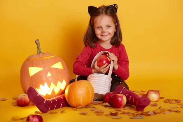 Porträt des kleinen mädchens im kostüm der katze, kind sitzt auf dem boden mit süßes oder saures-korb, umgeben von äpfeln und jack o lantern Premium Fotos