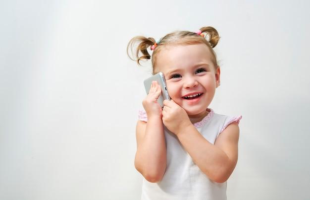 Porträt des kleinen mädchens ist positiv, dass die unterhaltung an einem telefon Premium Fotos