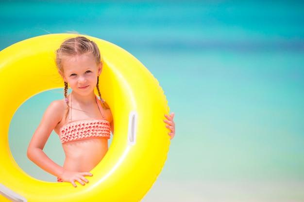 Porträt des kleinen mädchens mit aufblasbarem gummikreis auf strandferien Premium Fotos