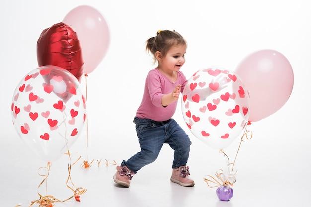 Porträt des kleinen mädchens spielend mit ballonen Kostenlose Fotos