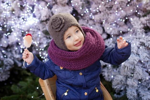 Porträt des kleinen mädchens zur weihnachtszeit im freien. Premium Fotos