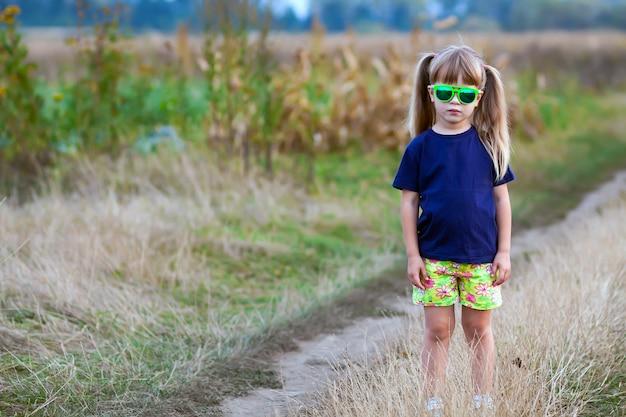 Porträt des kleinen modernen mädchens in der grünen sonnenbrille draußen Premium Fotos