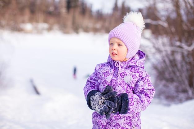 Porträt des kleinen netten glücklichen mädchens am sonnigen wintertag des schnees Premium Fotos
