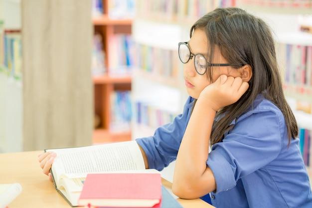 Porträt des klugen studenten mit offenem buch es in der collegebibliothek lesend Kostenlose Fotos