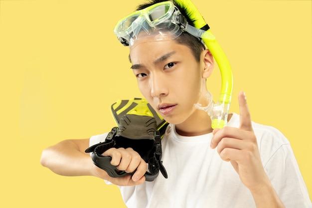 Porträt des koreanischen jungen mannes. männliches modell im weißen hemd und in der schutzbrille. flossen halten. konzept der menschlichen gefühle, ausdruck, sommerzeit, urlaub, wochenende. Kostenlose Fotos