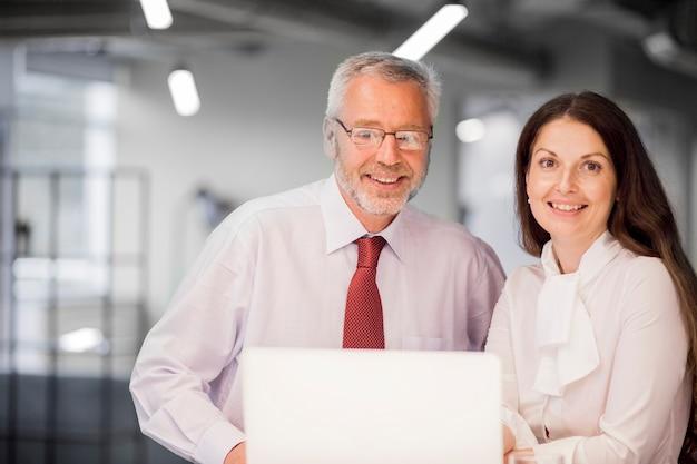 Porträt des lächelnden älteren geschäftsmannes und der geschäftsfrau mit laptop im büro Kostenlose Fotos