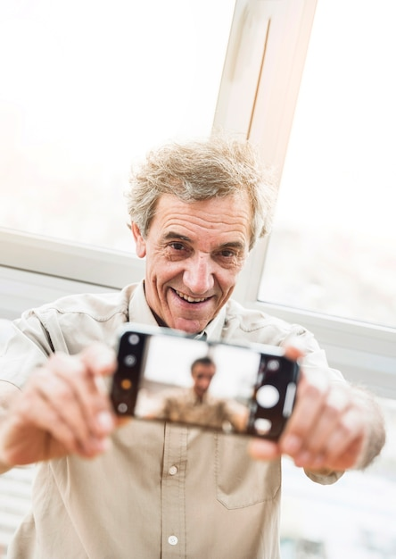 Porträt des lächelnden älteren mannes, der selfie mit smartphone nimmt Kostenlose Fotos
