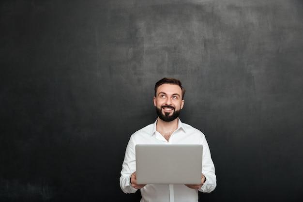 Porträt des lächelnden bärtigen mannes, der silbernen personal-computer hält und aufwärts, lokalisiert über dunkelgrauer wand schaut Kostenlose Fotos
