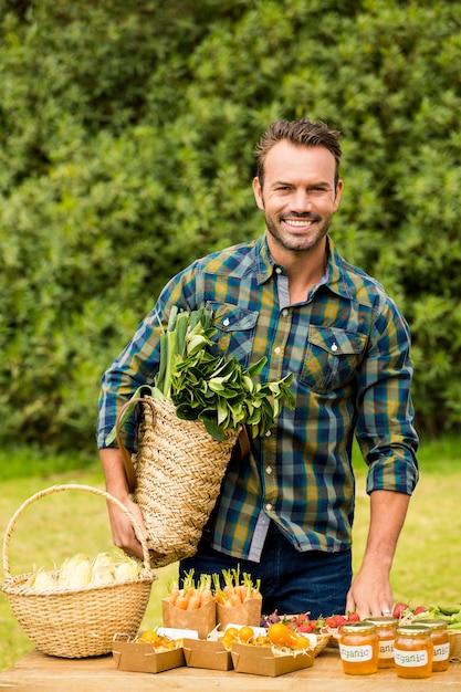Porträt des lächelnden gutaussehenden mannes organisches gemüse verkaufend Premium Fotos