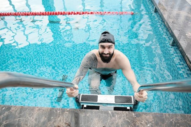 Porträt des lächelnden jungen bärtigen schwimmers in der schwarzen kappe, die aus dem wasser unter verwendung der treppe im pool herauskommt Premium Fotos