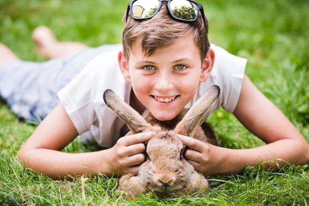 Porträt des lächelnden jungen liegend über kaninchen auf grünem gras im park Kostenlose Fotos