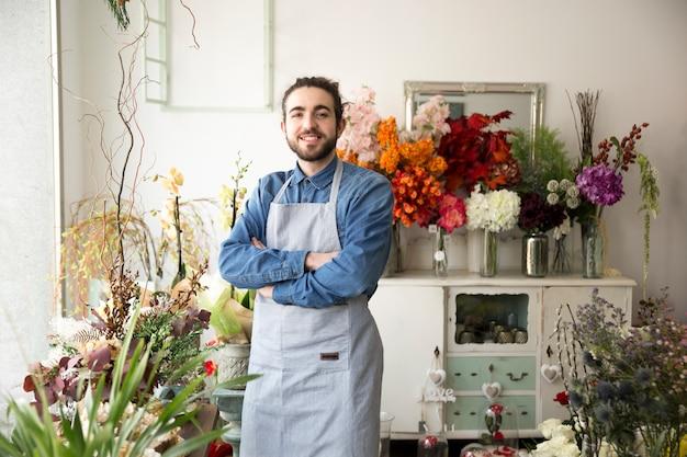 Porträt des lächelnden jungen männlichen floristen mit dem arm kreuzte in seinem blumenladen Kostenlose Fotos