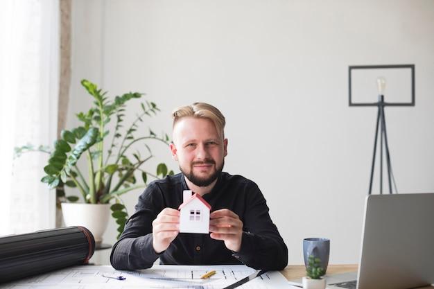 Porträt des lächelnden jungen mannes, der das hausmodell sitzt im büro betrachtet kamera hält Kostenlose Fotos