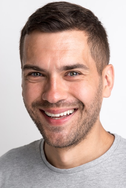 Porträt des lächelnden jungen mannes im grauen t-shirt, das kamera betrachtet Kostenlose Fotos