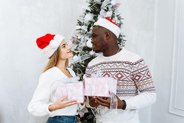 Porträt des lächelnden jungen paares nahe weihnachtsbaum feiern neujahr zusammen. Premium Fotos