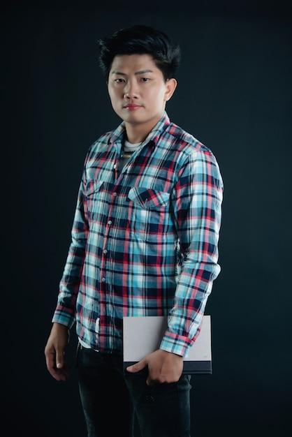 Porträt des lächelnden jungen studenten mit büchern Kostenlose Fotos