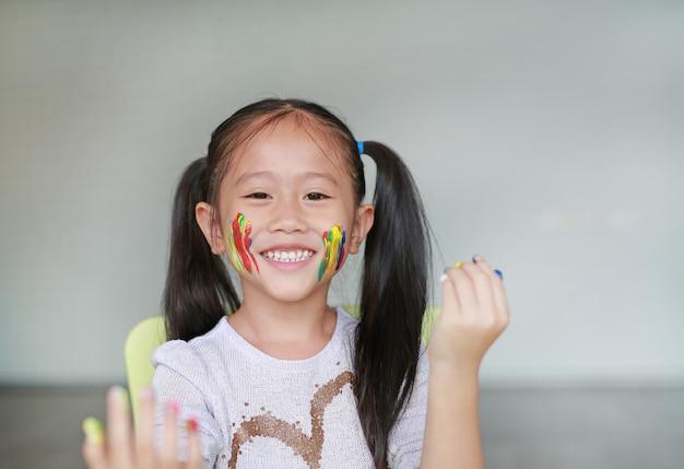 Porträt des lächelnden kleinen mädchens, das durch ihre bunten hände und backe gemalt im kinderraum schaut. Premium Fotos