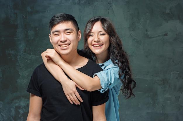 Porträt des lächelnden koreanischen paares auf einem grauen studiohintergrund Kostenlose Fotos