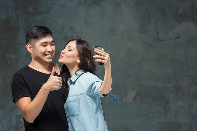 Porträt des lächelnden koreanischen paares, das selfie-foto auf einem grauen studiohintergrund macht Kostenlose Fotos