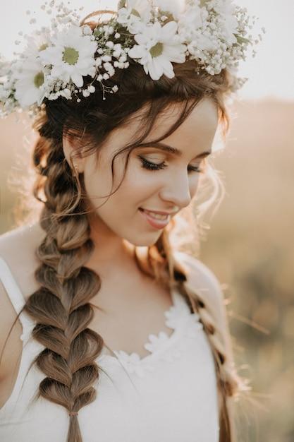 Porträt des lächelnden mädchens im weißen kleid mit blumenkranz und borten im sommer bei sonnenuntergang auf dem gebiet Premium Fotos