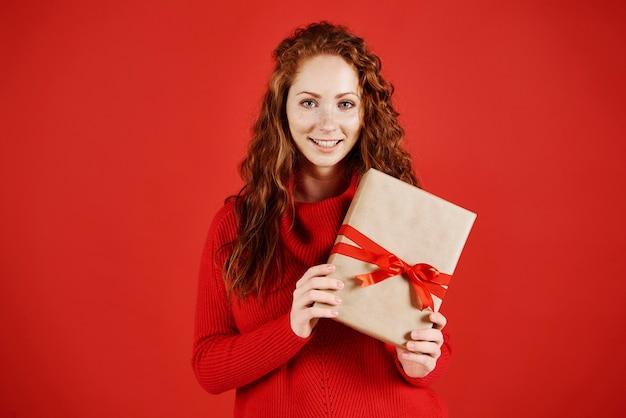 Porträt des lächelnden mädchens mit weihnachtsgeschenk Kostenlose Fotos