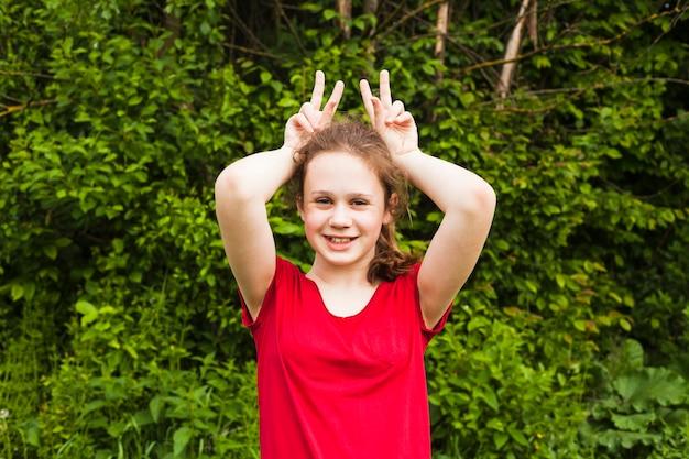Porträt des lächelnden mädchens neckend mit dem finger an hand im park Kostenlose Fotos