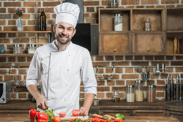 Porträt des lächelnden männlichen chefs, der hinter dem küchenthekeausschnittgemüse steht Kostenlose Fotos