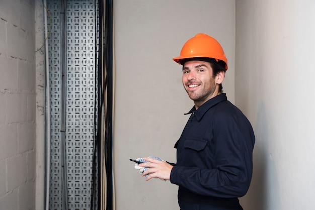 Porträt des lächelnden männlichen elektrikers, der kamera betrachtet Kostenlose Fotos