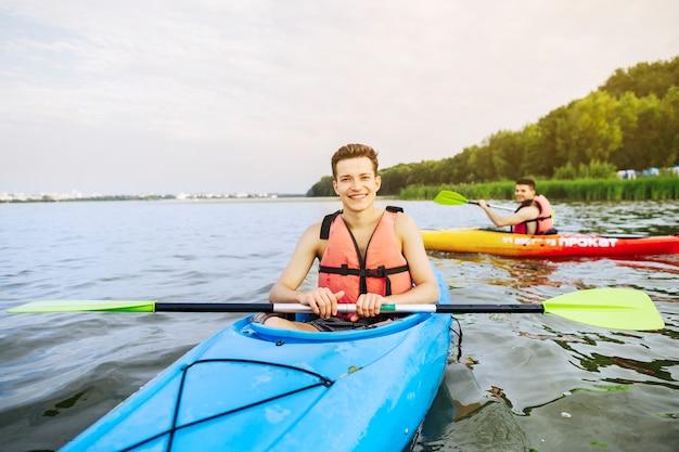 Porträt des lächelnden männlichen kayaker, der auf see kayak fährt Kostenlose Fotos